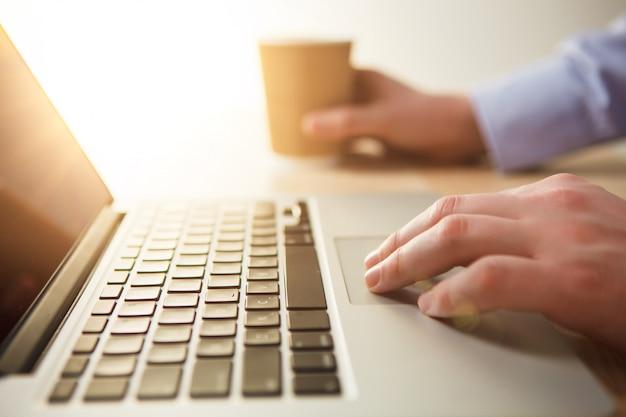 Mano sulla tastiera e caffè