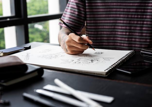 Mano tatuata che disegna opere d'arte