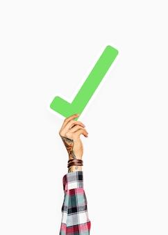 Mano tatuata che tiene l'icona del segno di spunta verde