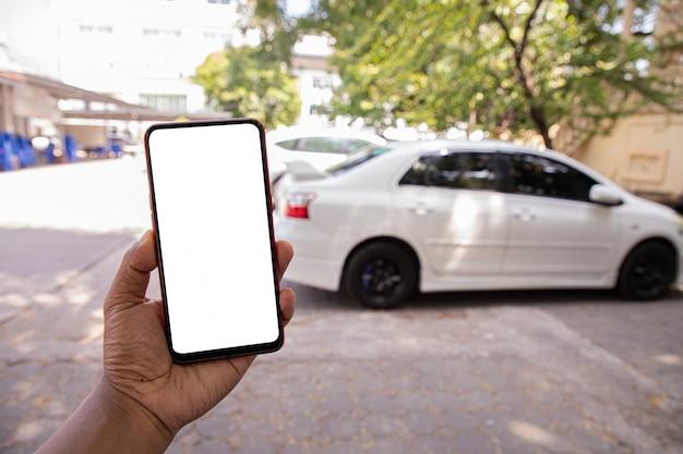 Mano tenere schermo vuoto sul cellulare, cellulare, tablet su auto bianca sfocata.