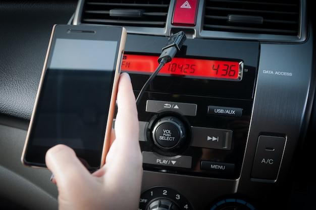 Mano tenere smartphone in auto, persone premere il telefono durante la guida