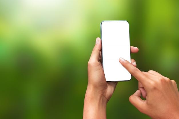 Mano toccando uno smartphone e uno schermo vuoto f