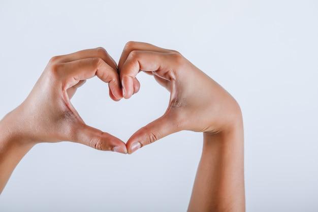 Mano umana che mostra forma del cuore con la mano