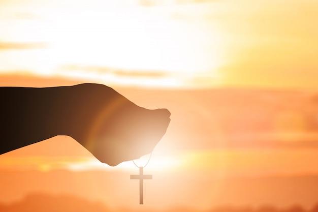 Mano umana che prega con la croce cristiana