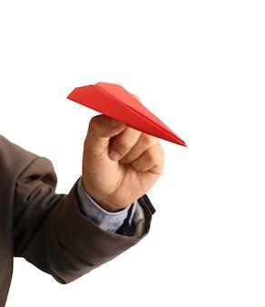 Mano umana che tiene aeroplano di carta rossa