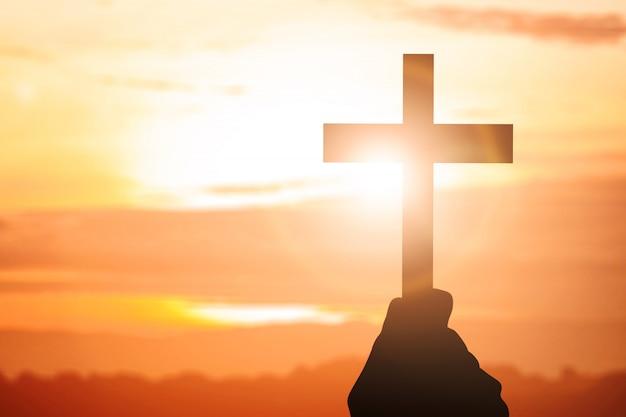 Mano umana che tiene croce cristiana