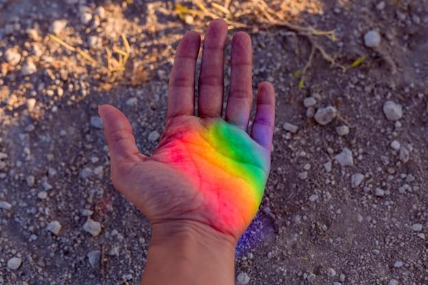 Mano umana con arcobaleno colorato riflesso su di lei.