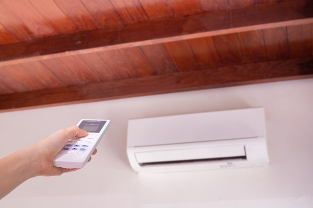 Mano umana premendo sul telecomando per accendere il condizionatore d'aria.