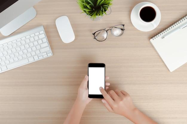 Mano utilizzare telefono cellulare schermo bianco sul tavolo di lavoro vista dall'alto
