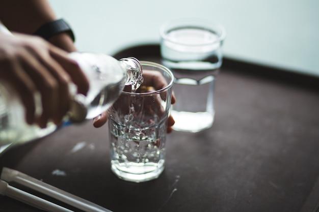 Mano versando acqua in una bottiglia di vetro