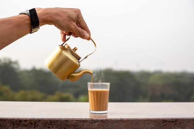 Mano versando il tè masala da una teiera in un bicchiere.