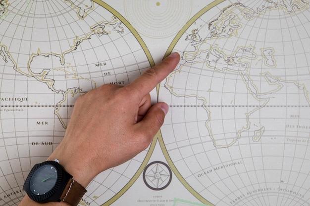 Mano vista dall'alto che punta sulla mappa del mondo