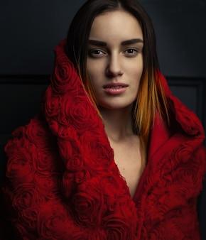 Mantello rosso della bella donna con le rose rosse dei fiori in studio