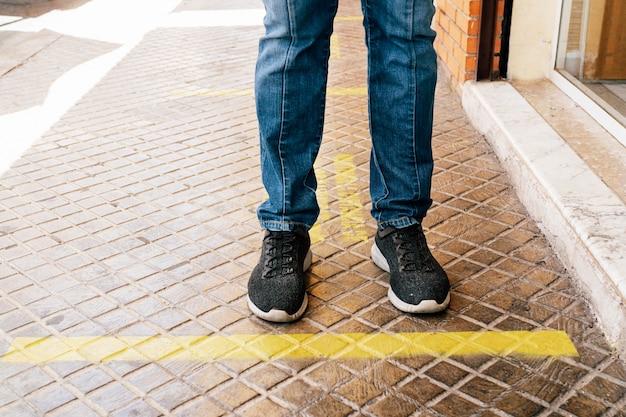 Mantieni la distanza sociale in giallo linea di attesa attaccata nel terreno. presunzione dei piedi di una persona.