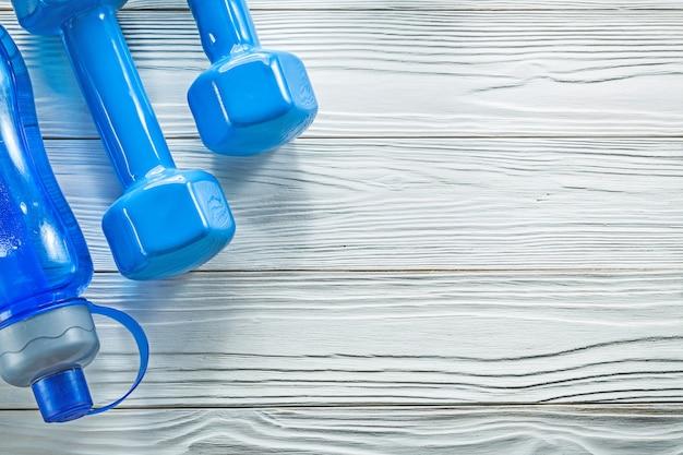 Manubri blu della bottiglia di acqua sul concetto di formazione sportiva del bordo di legno