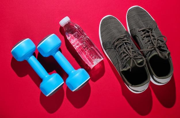 Manubri, bottiglia d'acqua, scarpe da ginnastica su superficie rossa