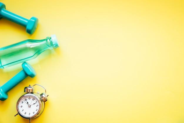 Manubri e bottiglia vicino sveglia