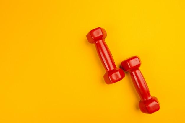 Manubri fitness su sfondo giallo brillante. concetto di fitness