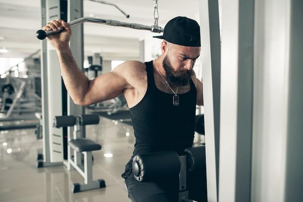 Manubri forte bodybuilder giovane di sollevamento
