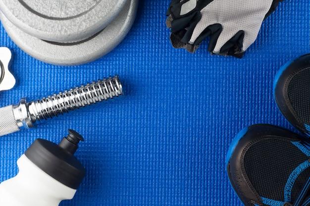 Manubri, guanti fitness, scarpe da ginnastica e bottiglia d'acqua sul tappetino yoga