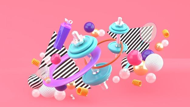 Manubri, racchette da badminton, bottiglie d'acqua e un hula hoop tra palline colorate sul rosa. rendering 3d.
