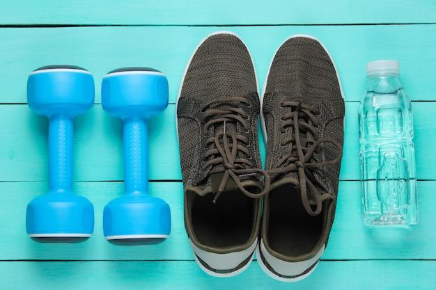 Manubri, scarpe da ginnastica, bottiglia d'acqua su superficie di legno blu.