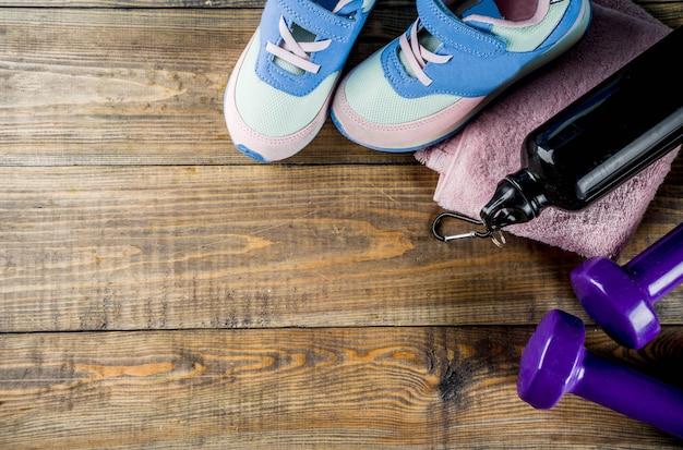 Manubri, scarpe da ginnastica, un asciugamano e una bottiglia di acqua su fondo in legno
