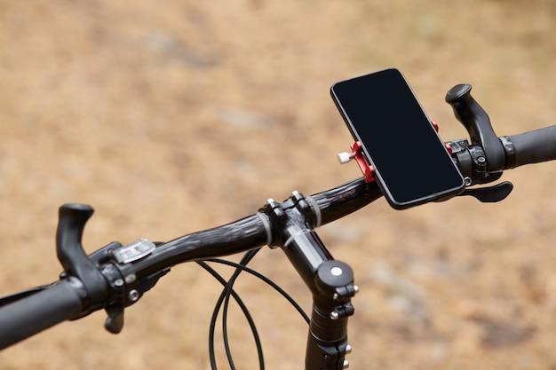 Manubrio nero di bicicletta sportiva su strada forestale