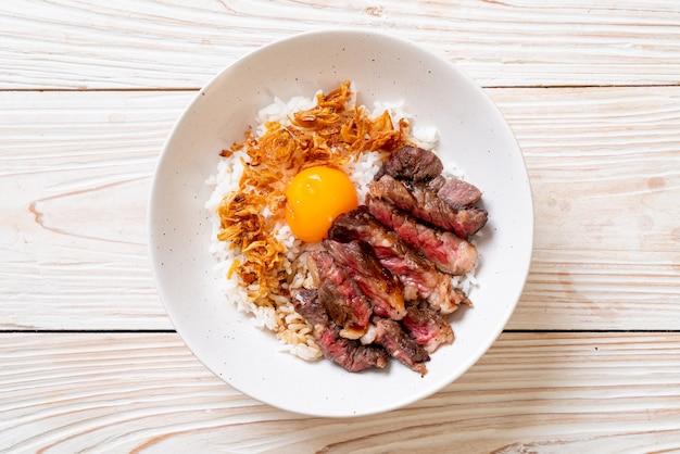 Manzo a fette sulla ciotola di riso sormontato con uovo