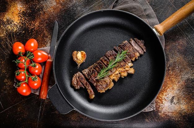 Manzo bistecca di new york in una padella. manzo premium di marmo.