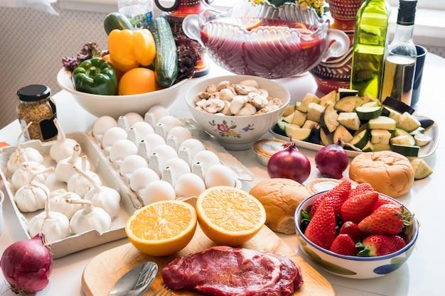 Manzo crudo cibo, uovo con verdure cibo sano, frutta preparata cucinare sul tavolo