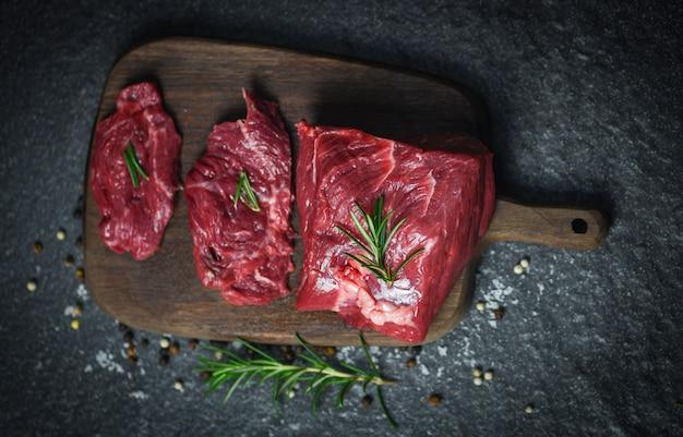 Manzo della carne fresca affettato su fondo nero - bistecca di manzo cruda con l'erba e le spezie sul tagliere di legno