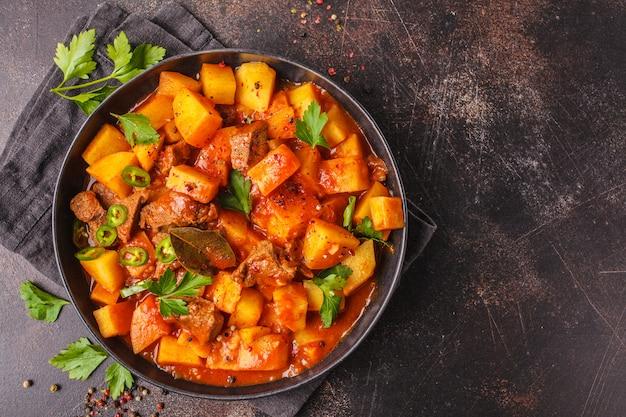 Manzo piccante in umido con patate in salsa di pomodoro in lamiera nera. gulasch di carne tradizionale.