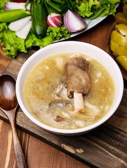 Manzo, zuppa di brodo di agnello con un pezzo di carne, salsa di pomodoro e cipolle, sumakh.
