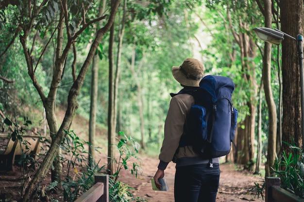 Mappa asiatica della tenuta dell'uomo con lo zaino e camminare nella foresta
