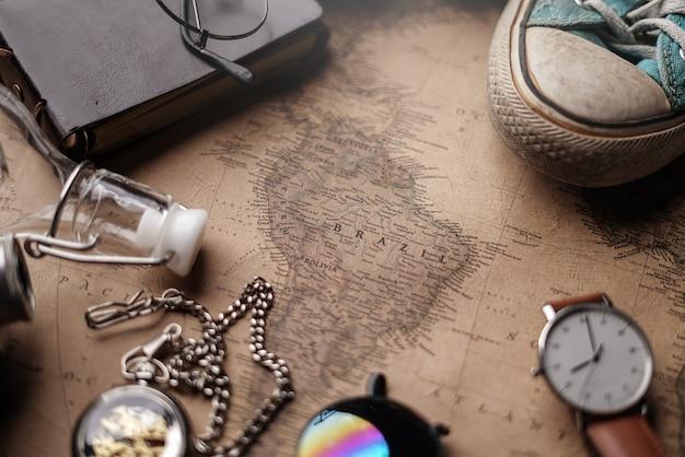 Mappa del brasile tra gli accessori del viaggiatore sulla vecchia mappa vintage.