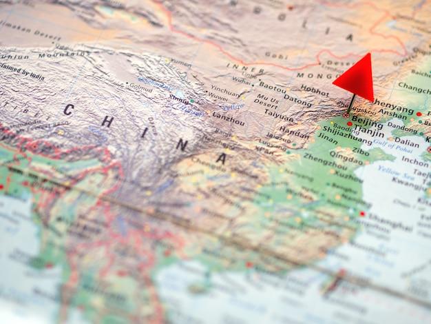 Mappa del mondo con particolare attenzione alla repubblica popolare cinese con la capitale pechino. puntina triangolare rossa su di esso.