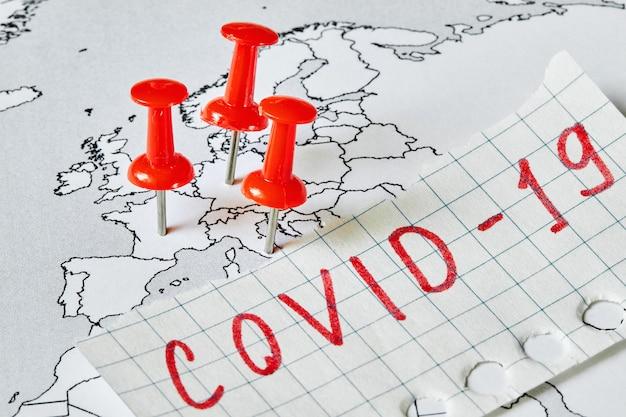Mappa dell'europa con simboli rossi in cui è covid-19 epidemia e la scritta covid-19 su un pezzo di carta. concetto di diffusione del virus.
