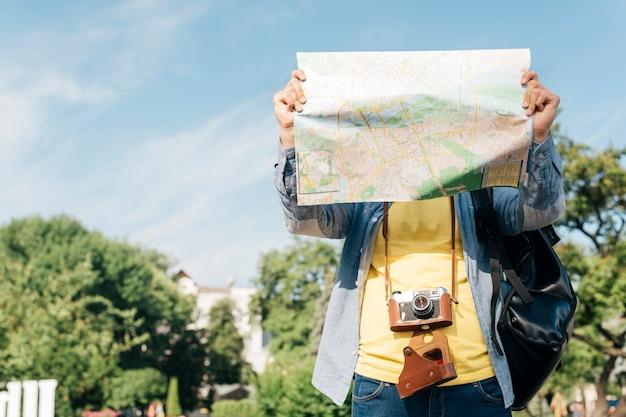 Mappa della tenuta dell'uomo del viaggiatore davanti al suo fronte con lo zaino e la macchina fotografica di trasporto