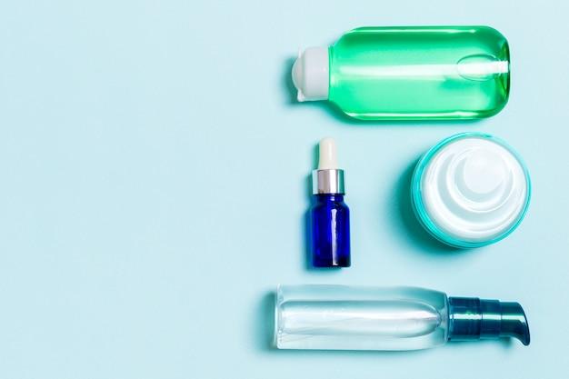 Marchio di cosmetici spa, set di tubi e vasetti di crema piatto giaceva su sfondo blu