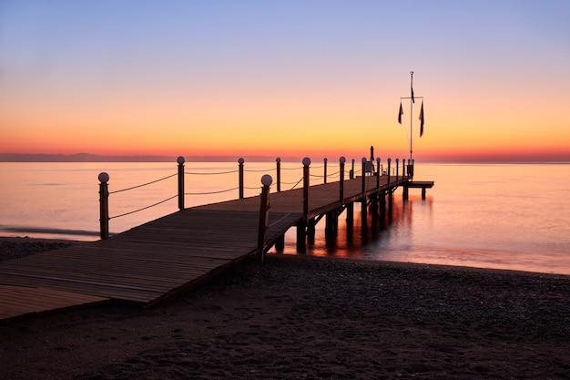 Mare calmo e caldo e un grande molo in legno con una piscina all'alba