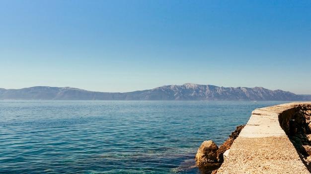Mare calmo e idilliaco con montagna e cielo blu chiaro