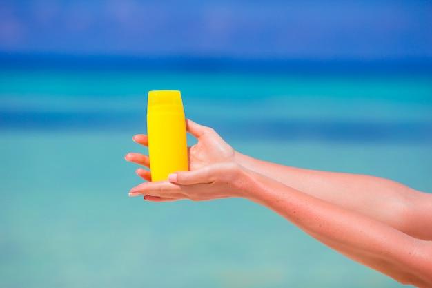 Mare del blu del fondo della bottiglia di crema solare del primo piano