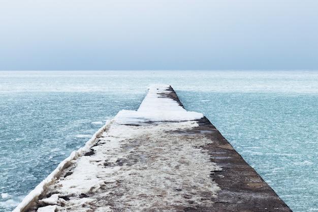 Mare ghiacciato e molo coperto di neve