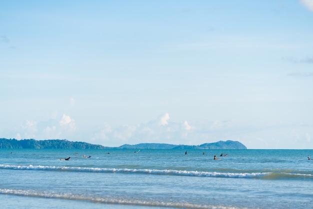 Mare limpido con surfista in acqua in attesa di onde / spiaggia di surf / attività estiva