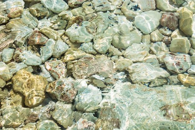Mare limpido, spiaggia di pietra. estate. modello. sfondo.
