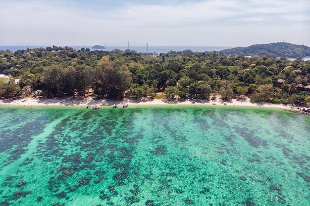 Mare tropicale smeraldo con barriera corallina e la spiaggia