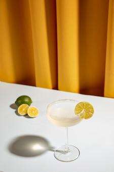 Margarita in vetro con calce sul tavolo bianco contro la tenda gialla