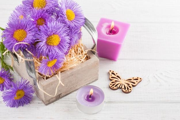 Margherite viola e candele accese sulla tabella bianca