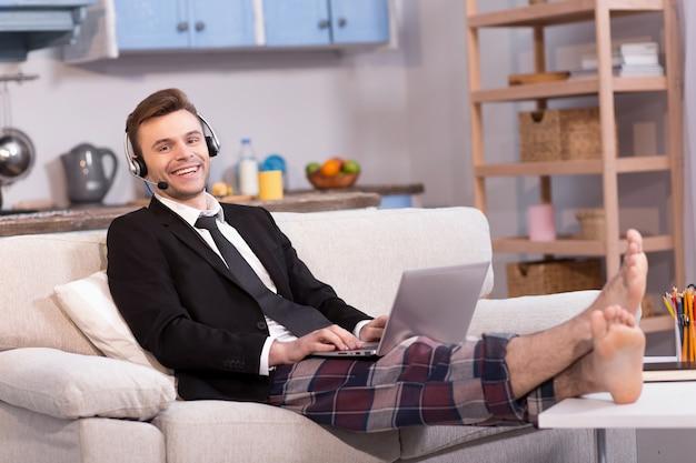 Marito che lavora freelance sorridendo guardando a porte chiuse.